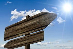 Indicios: dos señales de madera apuntando a sentidos contrarios