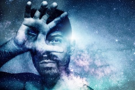 El rostro de un hombre cubierto por una mano con un ojo en la palma