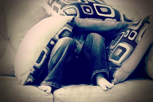 Esquema de la desconfianza, niño escondido tras cojines