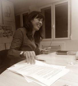 Isabel cogiendo unos relatos en su clase de proyectos narrativos